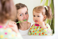Woman teaching child daughter teeth brushing in Royalty Free Stock Images