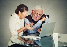 Woman teaching confused elderly man how to use laptop Royalty Free Stock Image