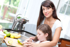 Woman teaching daughter kitchen safety. And attractive young women teaching her daughter kitchen safety and how to cook Royalty Free Stock Images