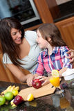 Woman teaching daughter kitchen safety. An attractive young women and mom teaching daughter kitchen safety and cooking Stock Photos