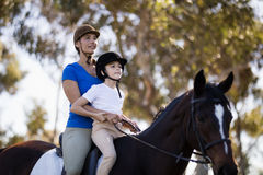 Woman teaching horseback riding to girl. Against tree Royalty Free Stock Image