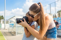 Woman teaching little girl to photograph using professional came Stock Image