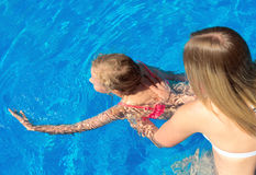Woman teaching little girl to swim. Place for text Royalty Free Stock Photo