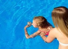 Woman teaching little girl to swim. Place for text Stock Photography
