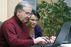 Woman teaching Senior use of computers Royalty Free Stock Photos