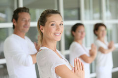 Woman teaching yoga to the group of people. Attractive blond women attending yoga course with group Stock Photo
