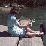 Woman in Teal Elbow Sleeve Mini Dress Reading Paper Near Body of Water during Daytime Royalty Free Stock Photos