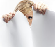 Woman tearing paper sheet. Young woman tearing a large sheet of paper stock photography