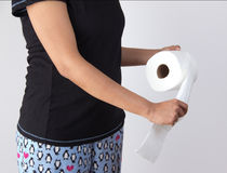 Woman tearing tissue from toilet paper roll. Woman in night pants tearing tissue from toilet paper roll Royalty Free Stock Images