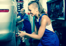 Woman technician fitting new tires to car at workshop Royalty Free Stock Images