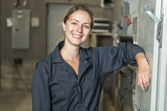 Woman Technician servicing at work on electric room royalty free stock photo