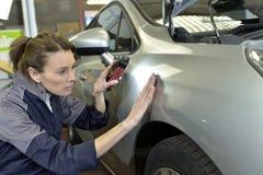 Woman technician working in a car shop stock photo