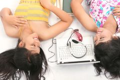 Woman and technology. Two girl lie down next by laptop Royalty Free Stock Photography