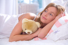 Woman with teddy bear in bed Stock Photos