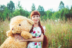 Woman with a Teddy bear in nature. Beautiful teen girl with Teddy bear in the park at green grass Royalty Free Stock Photo