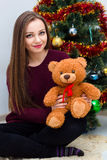 Woman with teddy bear near the Christmas tree Stock Image