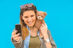Woman with teddy bear taking a selfie Royalty Free Stock Photo