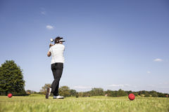 Woman teeing off. Stock Photography