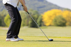 Woman teeing off, close up. Close up of senior female golf player teeing off ball on beautiful golf course stock image