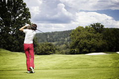 Woman teeing-off golf ball. Female golf player teeing-off golf ball at beautiful golf course with forest royalty free stock photos