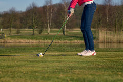 Woman teeing off at a golf course Royalty Free Stock Photography