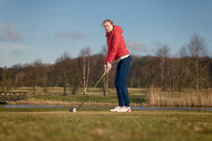Woman teeing off at a golf course. Woman teeing of on a golf course standing in the tee box in front of a water hazard with a driver in her hands ready to make a Royalty Free Stock Photography