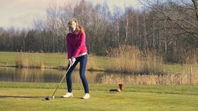 Woman teeing off at a golf course stock footage