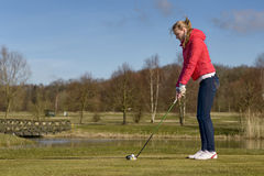 Woman teeing off at a golf course. Woman teeing of on a golf course standing in the tee box in front of a water hazard with a driver in her hands ready to make a Royalty Free Stock Photo