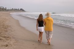 Woman and teen. Mother and daughter walking on the beach royalty free stock photo