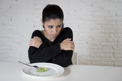 Woman or teen with fork eating dish with ridiculous little lettuce as her food symbol of crazy diet Stock Images