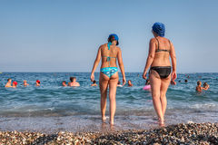 Woman and teen girl go into the sea water. Royalty Free Stock Image