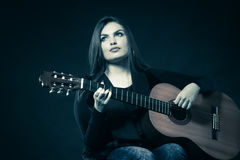 Woman teen girl with guitar on black Royalty Free Stock Photography