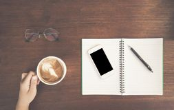 Woman teen ,Hand holding cup of coffee,With notebook and pen on wooden table. royalty free stock photo