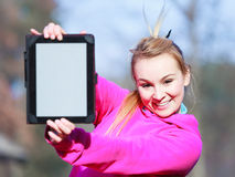 Woman teenage girl in pink tracksuit showing blank tablet outdoor. Fitness woman sport teenage girl in pink tracksuit showing blank copy space screen of tablet Stock Images