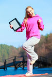 Woman teenage girl in pink tracksuit showing blank tablet outdoor. Full length of fitness woman sport teenage girl in pink tracksuit showing blank copy space Stock Images