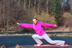 Woman teenage girl in tracksuit doing exercise on pier outdoor Stock Images