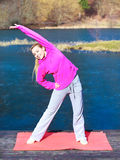Woman teenage girl in tracksuit doing exercise on pier outdoor. Full length of young woman teenage girl in pink tracksuit doing morning exercise on mat on pier Royalty Free Stock Photography