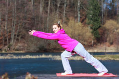 Woman teenage girl in tracksuit doing exercise on pier outdoor. Full length of young woman teenage girl in pink tracksuit doing morning exercise on mat on pier Royalty Free Stock Image