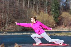 Woman teenage girl in tracksuit doing exercise on pier outdoor. Full length of young woman teenage girl in pink tracksuit doing morning exercise on mat on pier Stock Images