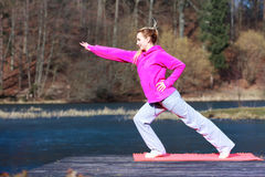 Woman teenage girl in tracksuit doing exercise on pier outdoor. Full length of young woman teenage girl in pink tracksuit doing morning exercise on mat on pier Royalty Free Stock Photos