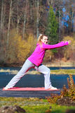 Woman teenage girl in tracksuit doing exercise on pier outdoor. Full length of young woman teenage girl in pink tracksuit doing morning exercise on mat on pier Royalty Free Stock Images