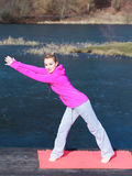 Woman teenage girl in tracksuit doing exercise on pier outdoor Royalty Free Stock Image