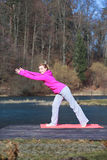 Woman teenage girl in tracksuit doing exercise on pier outdoor. Full length of young woman teenage girl in pink tracksuit doing morning exercise on mat on pier Stock Image