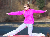 Woman teenage girl in tracksuit doing exercise on pier outdoor Royalty Free Stock Photography