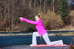 Woman teenage girl in tracksuit doing exercise on pier outdoor Stock Photos