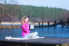 Woman teenage girl in tracksuit showing tablet on pier outdoor. Full length of fitness woman sport teenage girl in pink tracksuit showing blank copy space screen Royalty Free Stock Image