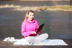 Woman teenage girl in tracksuit using tablet on pier outdoor. Full length of fitness woman sport teenage girl in tracksuit using tablet touchpad computer sitting Royalty Free Stock Photography