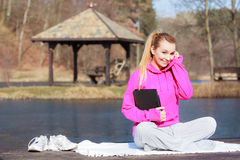Woman teenage girl in tracksuit using tablet on pier outdoor. Full length of fitness woman sport teenage girl in tracksuit using tablet touchpad computer sitting Stock Photo