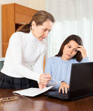 Woman and teenager daughter at table with notebook Royalty Free Stock Photos