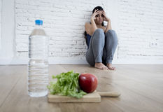 Woman or teenager girl sitting on ground alone worried at home suffering nutrition eating disorder Royalty Free Stock Image